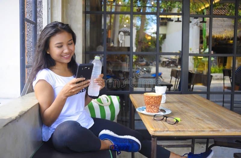 Schönes glückliches Asiatinlächeln entspannt, Frühstück unter Verwendung des Handys genießend lizenzfreie stockfotografie