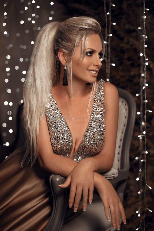 Schönes glückliches Blondineporträt mit den Quastenohrringen, die auf Sofa über bokeh sitzen, beleuchtet Weihnachtsdunkelheitshin stockbilder