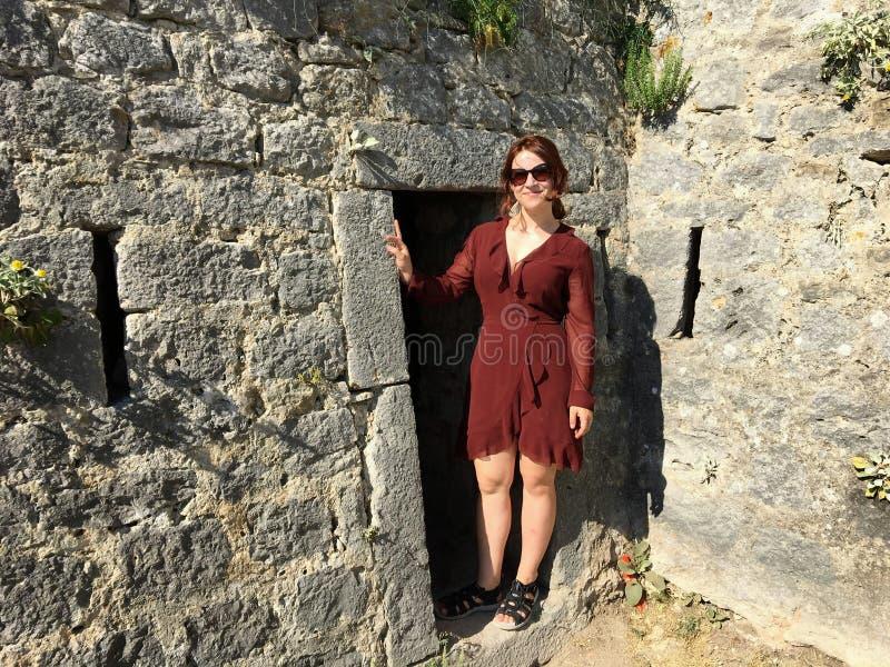 Schönes, glückliches, junges touristisches Anwesen neben einer Türe oder Eingängen zur antiken Festung Klis lizenzfreie stockbilder