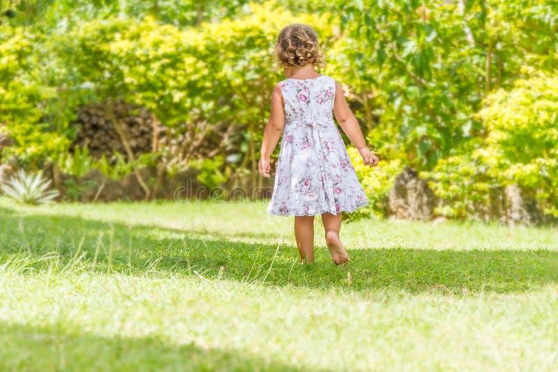 Schönes glückliches Kindermädchen, das auf natürlicher Rückseite im Freien läuft lizenzfreie stockfotografie