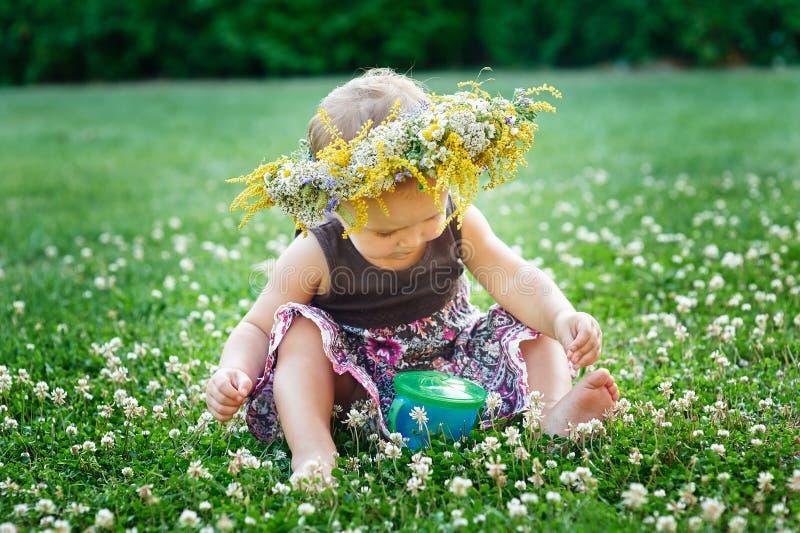 Schönes glückliches kleines Baby in einem Kranz auf einer Wiese auf der Natur stockfotografie
