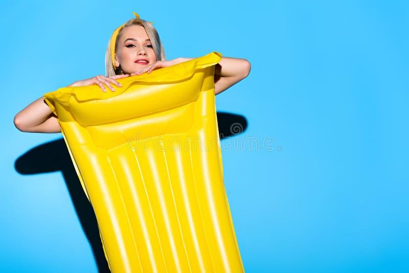 schönes glückliches Mädchen, das mit gelber aufblasbarer Matratze aufwirft lizenzfreies stockfoto