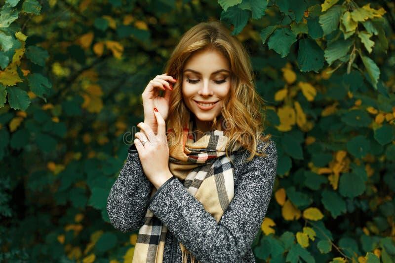 Schönes glückliches Mädchen in einem Weinleseschal und -mantel auf einem Gelb stockfotografie