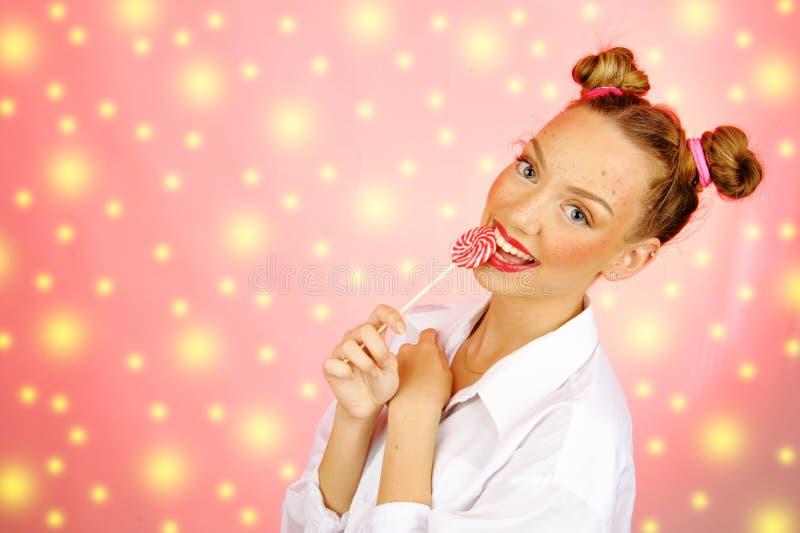 Schönes glückliches Mädchen mit den Sommersprossen, die Bonbonsüßigkeitslutscher mit Gesichtsausdruck halten und essen lizenzfreie stockfotos