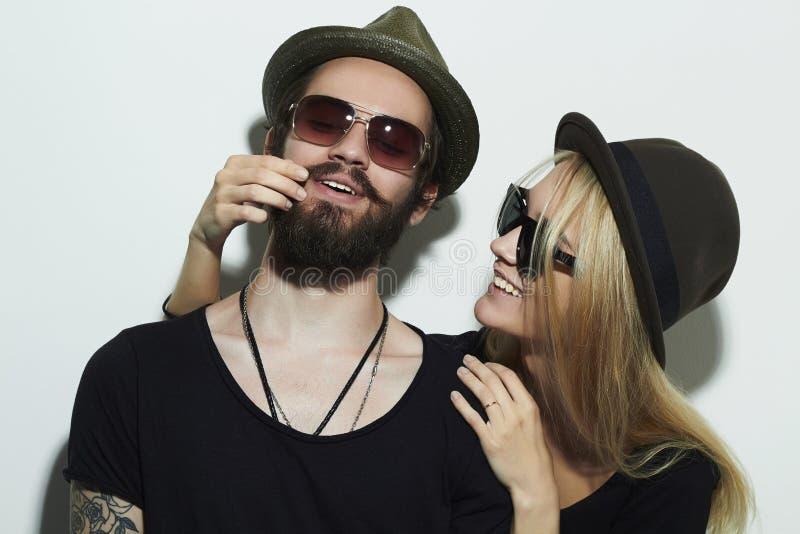 Schönes glückliches Paar im Hut, der zusammen modische Gläser trägt stockbilder