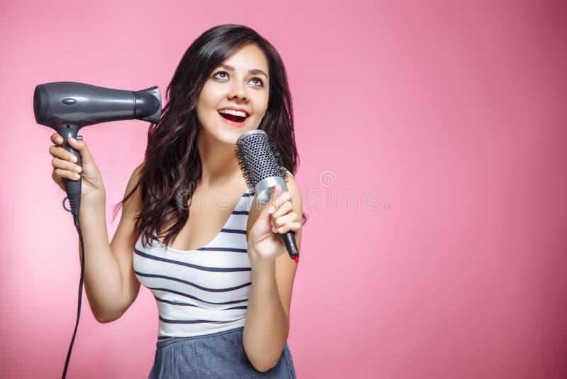 Schönes glückliches und bei der Anwendung eines hairdryer und der Haarbürste auf rosa Hintergrund singendes Gefühl der jungen Fra stockfoto