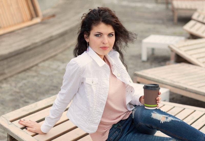 Schönes großes Mädchen mit langem Haar Brunette in den Jeans, die auf alten hölzernen Planken mit einem Tasse Kaffee in der Hand  lizenzfreies stockfoto