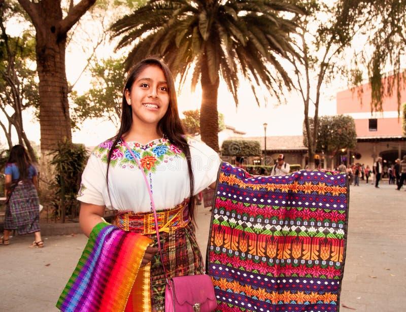 Schönes guatamalian Mädchen, das traditionelles buntes Gewebe salling ist lizenzfreie stockbilder