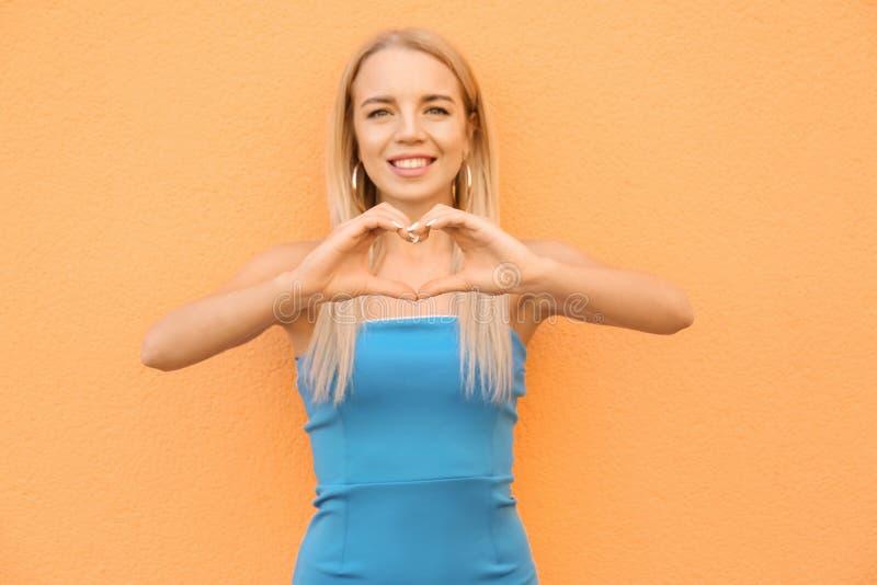 Schönes Händchenhalten der jungen Frau in Form des Herzens nahe Farbwand lizenzfreie stockfotografie