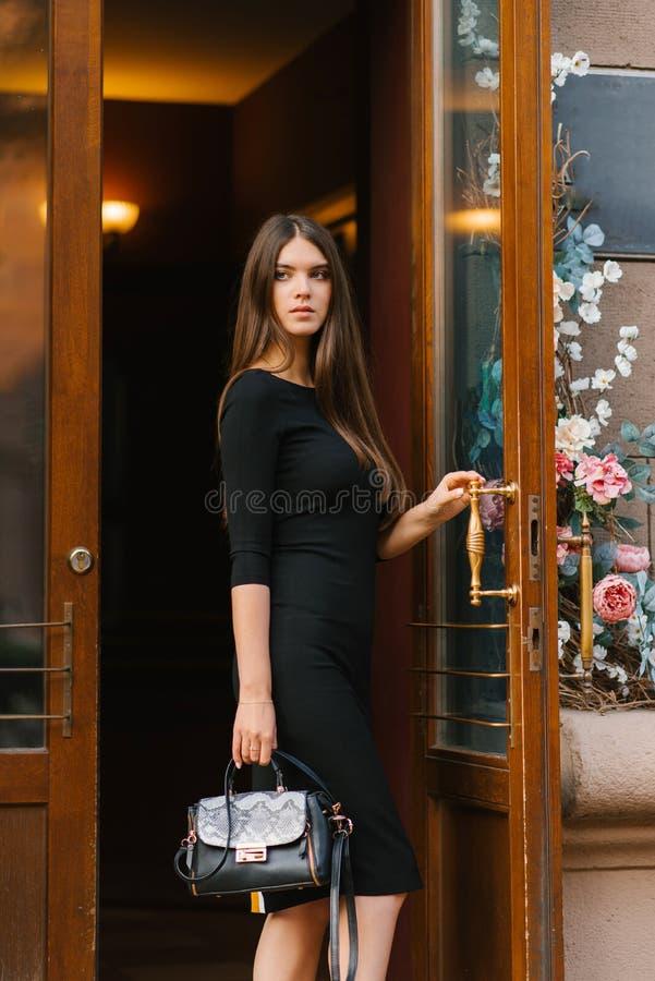 Schönes hübsches Mädchen in einem schwarzen Kleid mit einer schwarzen Tasche, sie öffnet die schönen Holztüren zu Haus oder Gesch lizenzfreies stockfoto