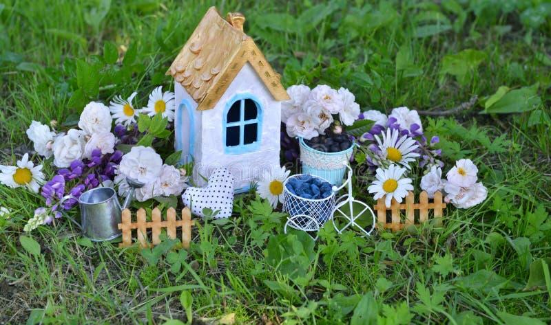 Schönes Haus mit Wildflowers, Zaun und Gießkanne stockbilder