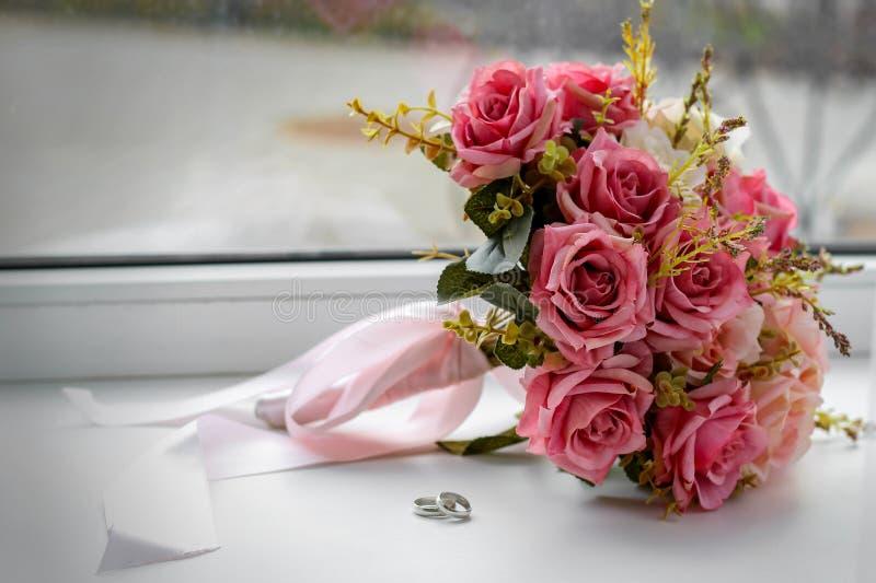 Schönes Heiratsstillleben mit einem Blumenstrauß und Ringen stockbilder