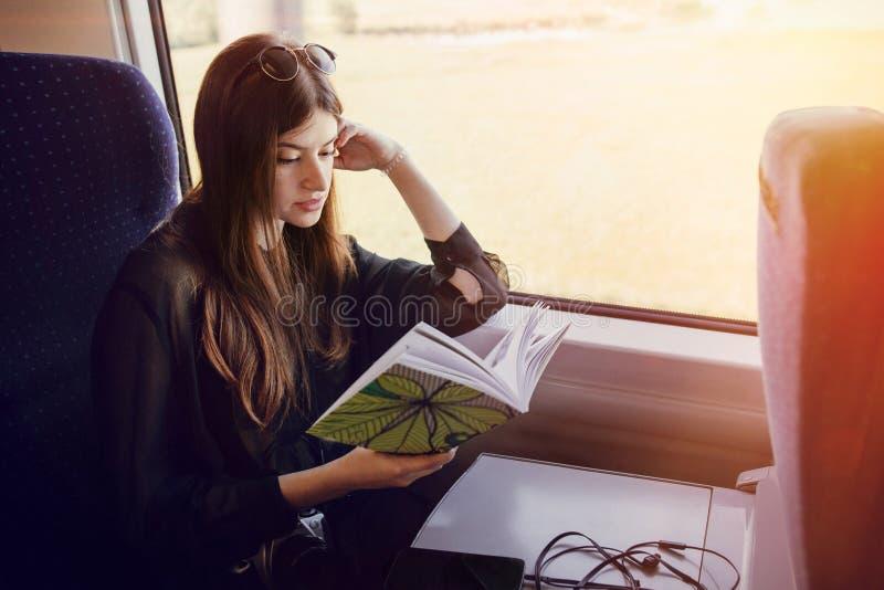 Schönes Hippie-Mädchen, das mit dem Zug reist und Buch hält Styl stockbild