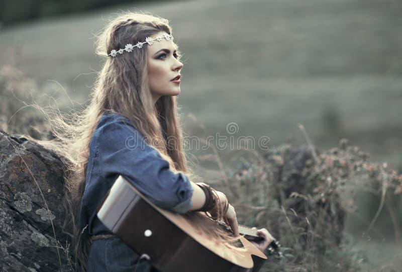 Schönes Hippiemädchen mit Gitarre stockfotografie