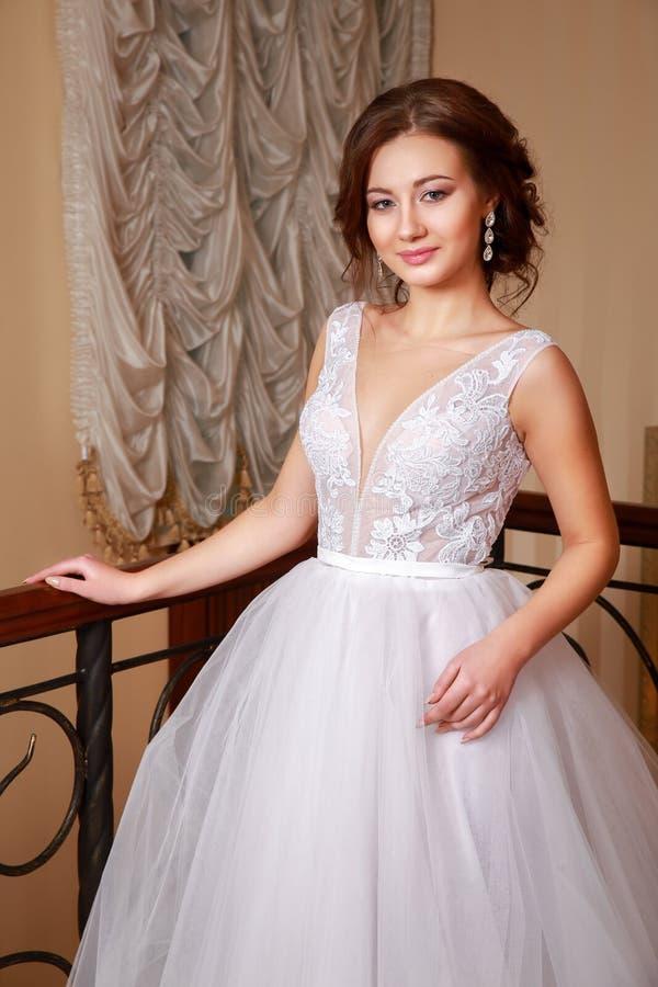 Schönes Hochzeitskleid Hübsche Braut im Hochzeitskleid in einer Luxuswohnung stockbild