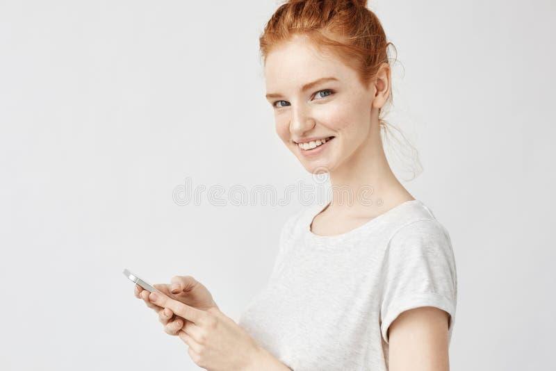 Schönes Ingwermädchen, das das Telefon halten twitting oder verwendet worden sein würden Social Media über weißer Wand lächelt lizenzfreie stockbilder