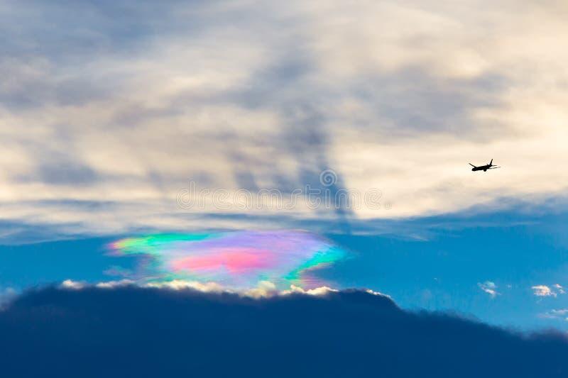 Schönes irisation mit dem Flugzeug während der Sonnenuntergangumwelt stockbild