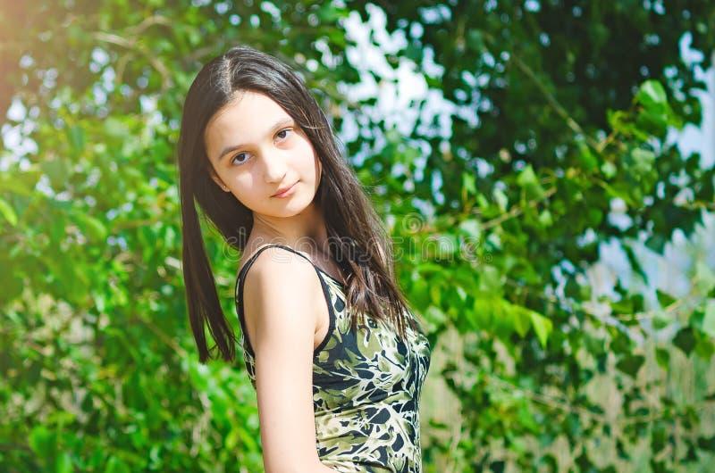Schönes jugendlich Mädchen auf einem grünen Baumhintergrund lizenzfreie stockfotografie