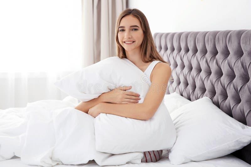 Schönes jugendlich Mädchen, das bequemes Kissen im Bett umarmt lizenzfreie stockfotografie