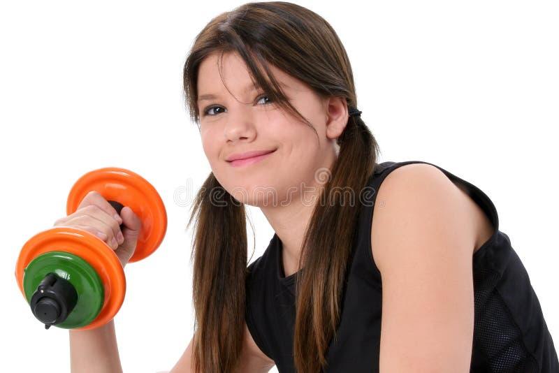 Schönes jugendlich Mädchen, das bunte Gewichte über Weiß anhält stockbild