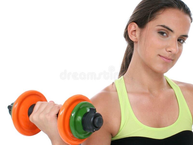Schönes jugendlich Mädchen, das bunte Gewichte anhält lizenzfreies stockbild
