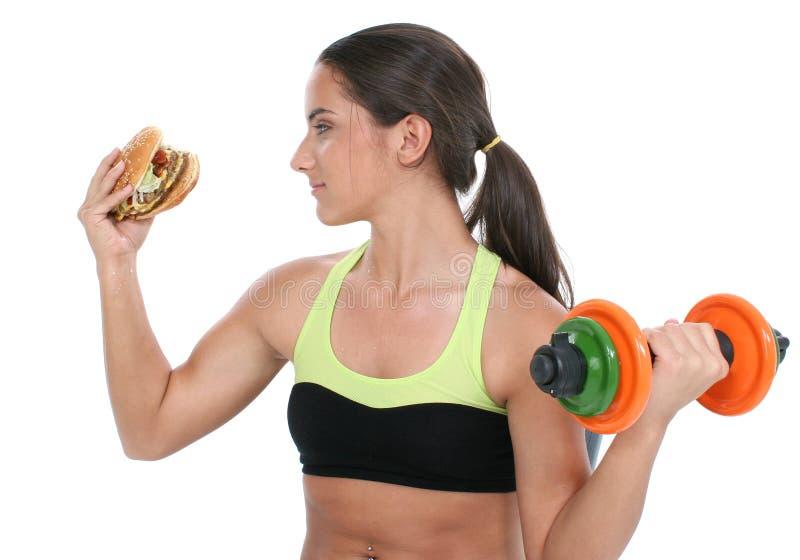 Schönes jugendlich Mädchen, das bunte Gewichte und ein riesiges Cheeseb anhält stockfotos