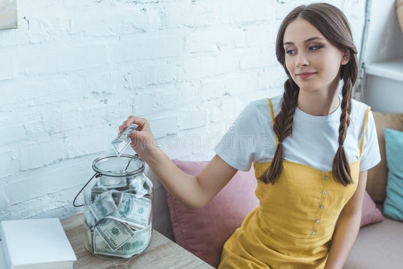 schönes jugendlich Mädchen, das Dollarbanknote in Einsparung setzt stockbild