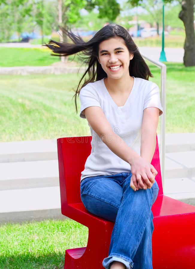 Schönes jugendlich Mädchen, das draußen auf rotem Stuhl sitzt lizenzfreie stockfotos