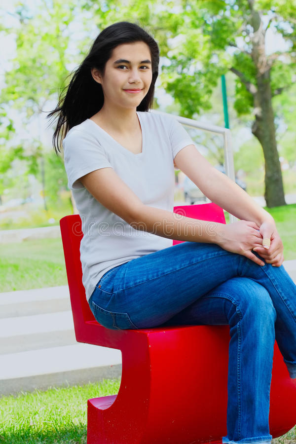 Schönes jugendlich Mädchen, das draußen auf rotem Stuhl sitzt stockbilder