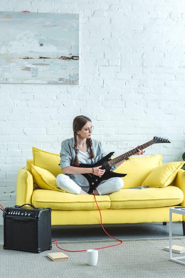 schönes jugendlich Mädchen, das E-Gitarre auf Sofa spielt stockfotografie