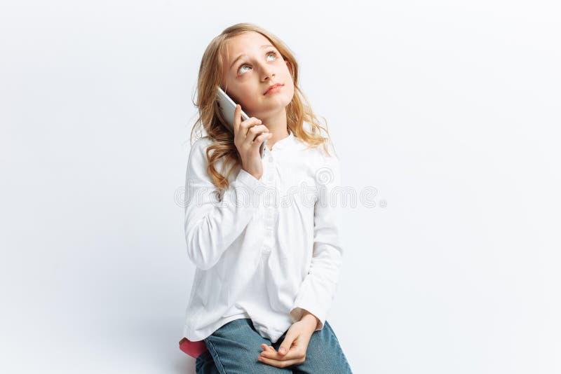 Schönes jugendlich Mädchen, das am Handy, Foto Studio, lokalisiert spricht lizenzfreie stockbilder