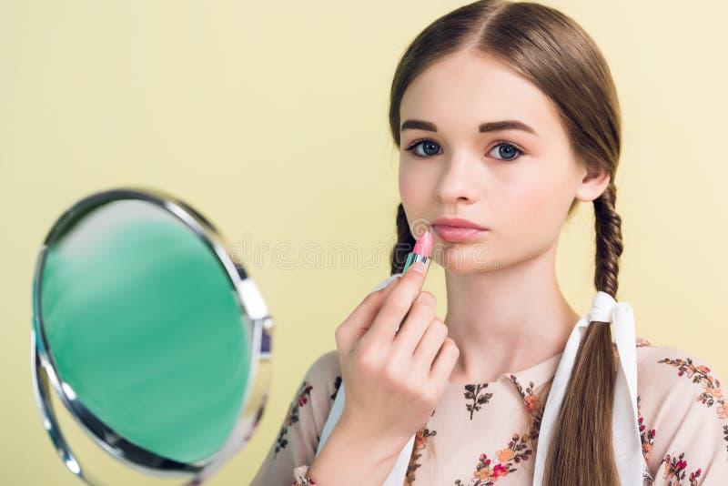 schönes jugendlich Mädchen, das Lippenstift mit Spiegel anwendet lizenzfreie stockfotografie