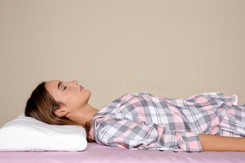 Schönes jugendlich Mädchen, das mit orthopädischem Kissen auf Bett gegen Farbhintergrund schläft lizenzfreies stockbild