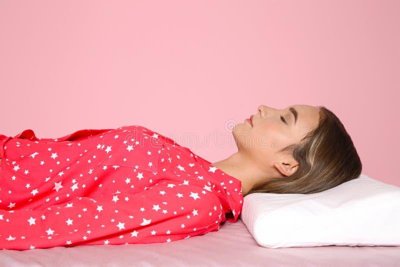 Schönes jugendlich Mädchen, das mit orthopädischem Kissen auf Bett schläft stockfotos