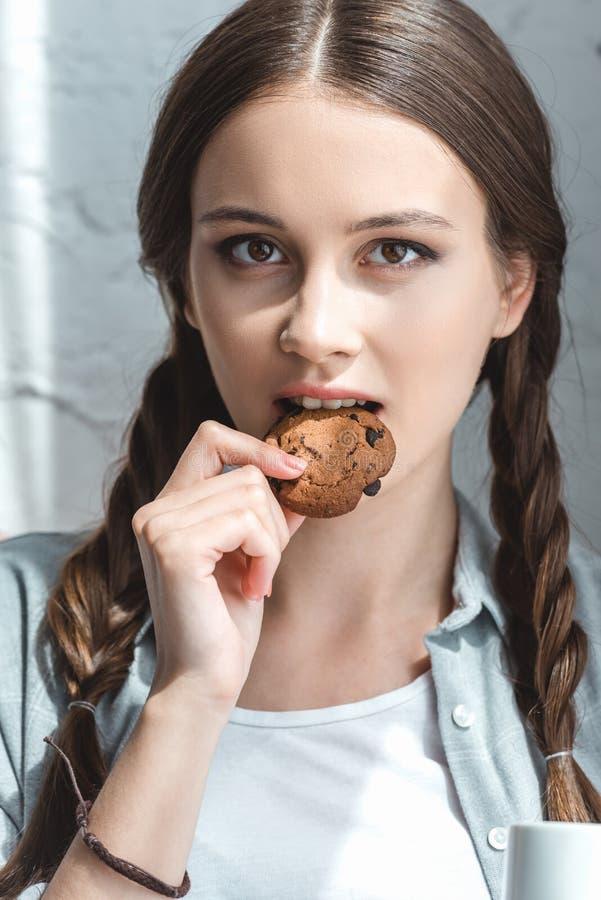 schönes jugendlich Mädchen, das Plätzchen und das Schauen isst stockfotografie