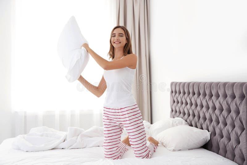 Schönes jugendlich Mädchen, das Spaß mit Kissen im Bett hat lizenzfreies stockfoto