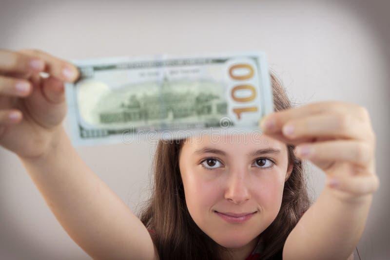 Schönes jugendlich Mädchen, das US-Dollars hält lizenzfreie stockbilder