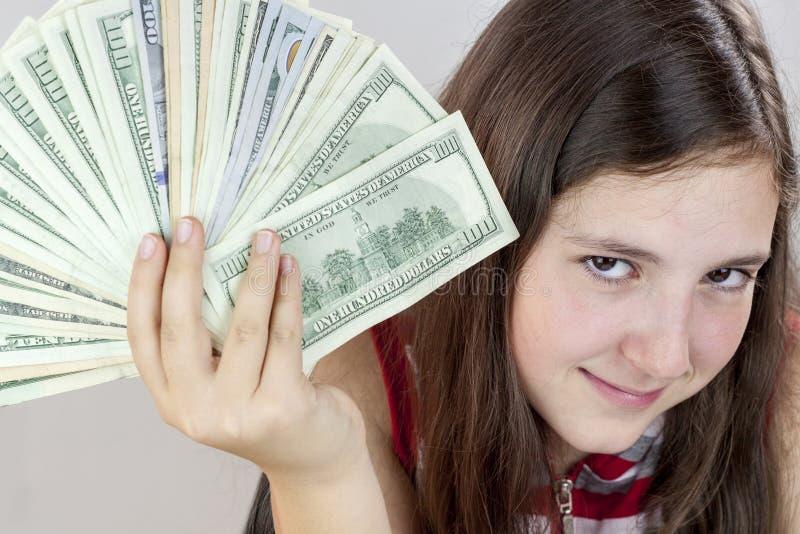 Schönes jugendlich Mädchen, das US-Dollars hält stockfoto