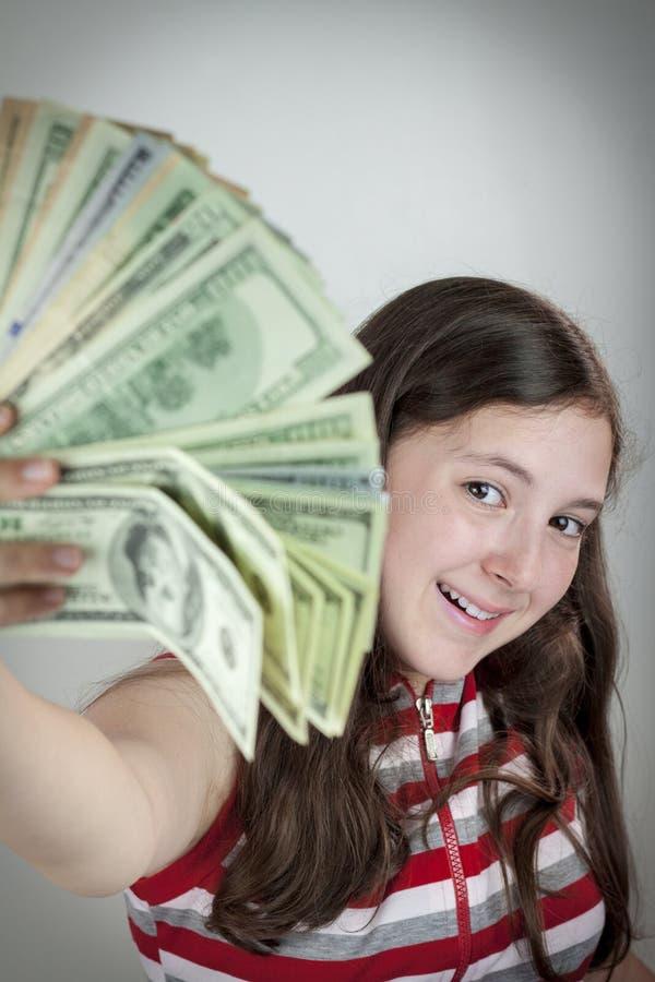 Schönes jugendlich Mädchen, das US-Dollars hält lizenzfreies stockfoto