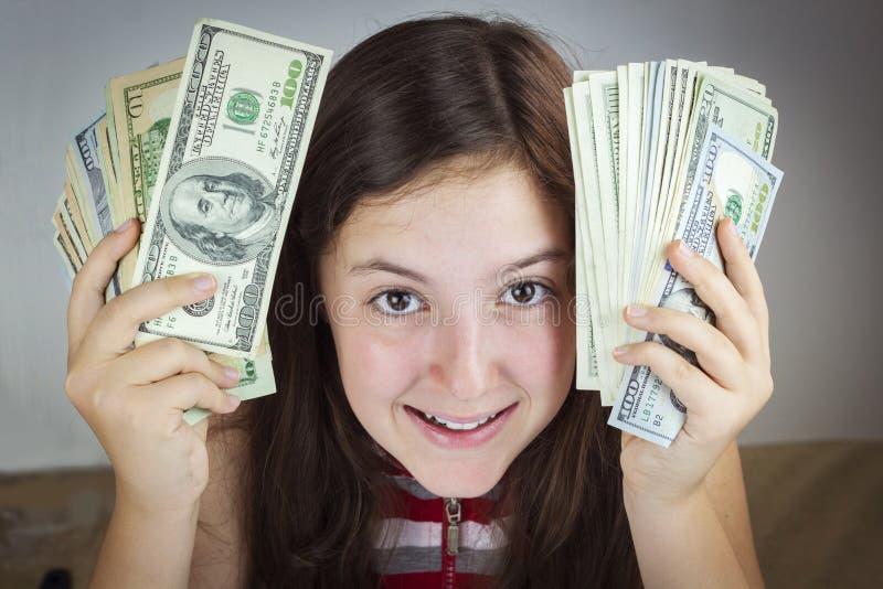 Schönes jugendlich Mädchen, das US-Dollars hält stockfotos