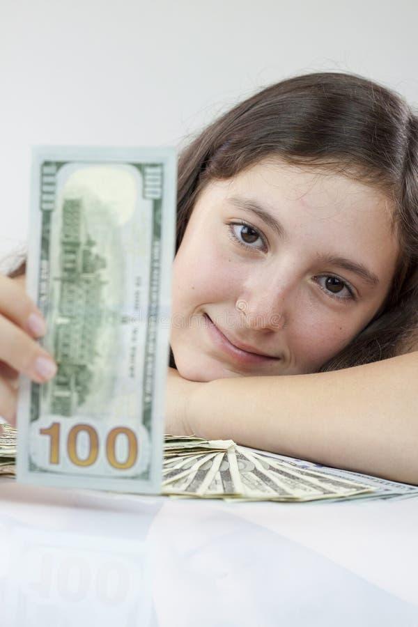 Schönes jugendlich Mädchen, das US-Dollars hält lizenzfreies stockbild