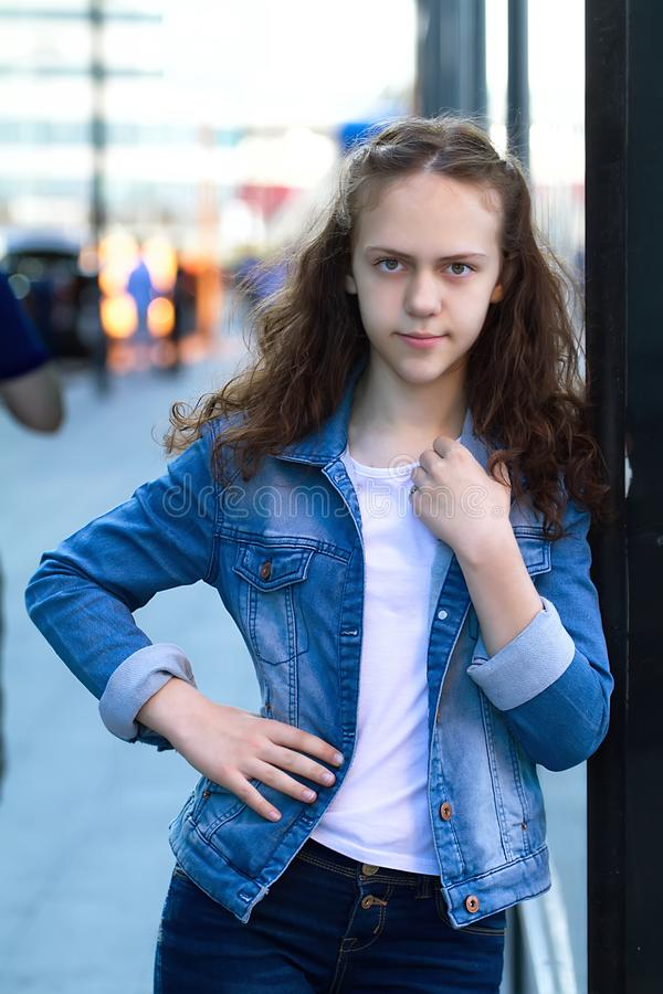 Schönes jugendlich Mädchen in der Denimkleidung steht, lehnend auf einem Glasgebäude auf der Stadtstraße stockbilder