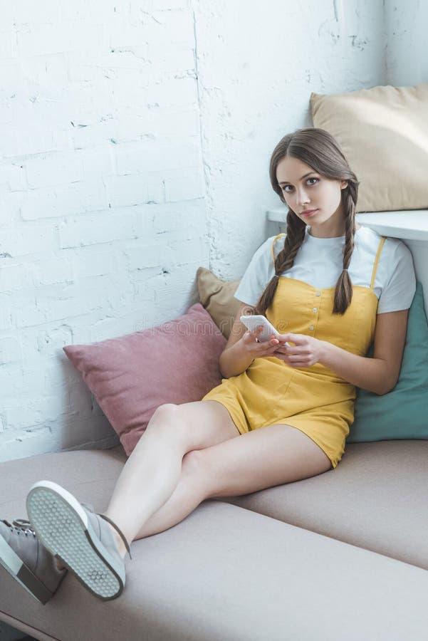 schönes jugendlich Mädchen mit Borten unter Verwendung des Smartphone und des Sitzens lizenzfreie stockbilder