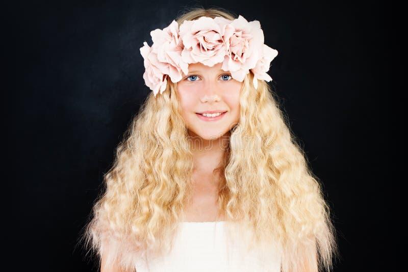 Schönes jugendlich Mädchen mit dem blonden gelockten Haar und den Blumen auf Dunkelheit lizenzfreies stockbild