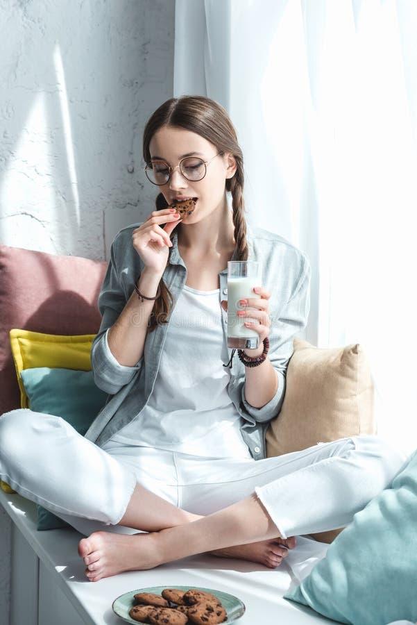 schönes jugendlich Mädchen mit dem Glas Milch Plätzchen essend lizenzfreie stockfotos