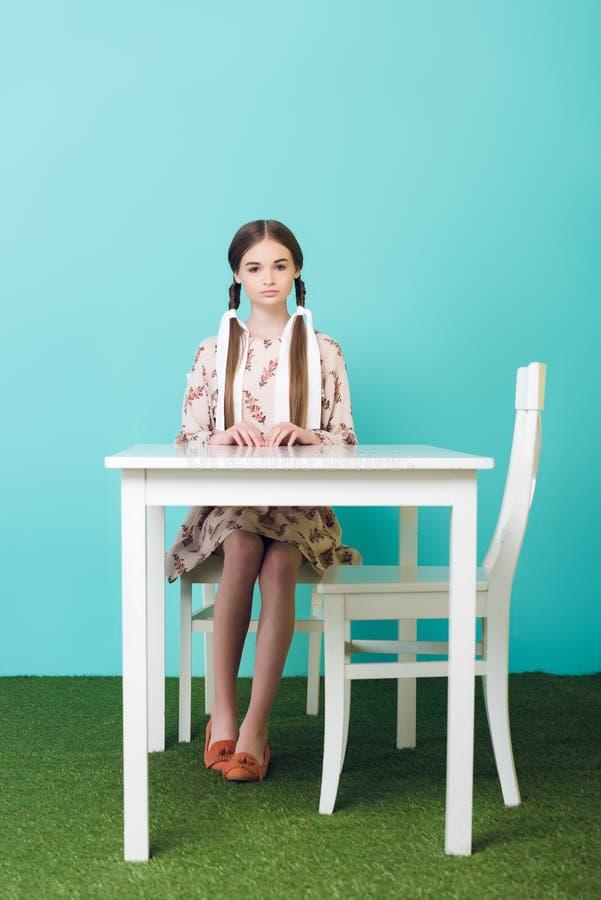 schönes jugendlich Mädchen mit den Borten, die bei Tisch sitzen stockfotos