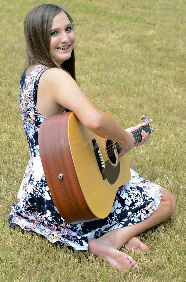 Schönes jugendlich Mädchen mit Gitarre stockfoto