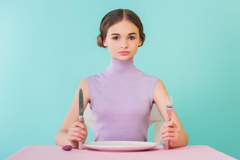 schönes jugendlich Mädchen mit Messergabel und leerem Plattensitzen stockfotografie