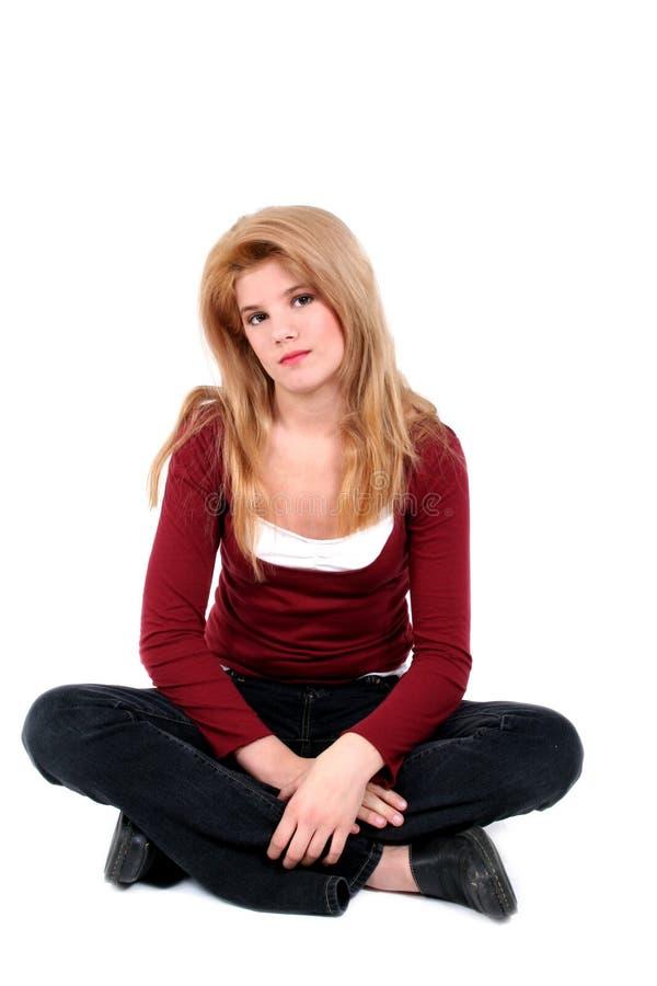 Schönes jugendlich Mädchen-sitzende Fahrwerkbeine gekreuzt auf Weiß. stockfoto