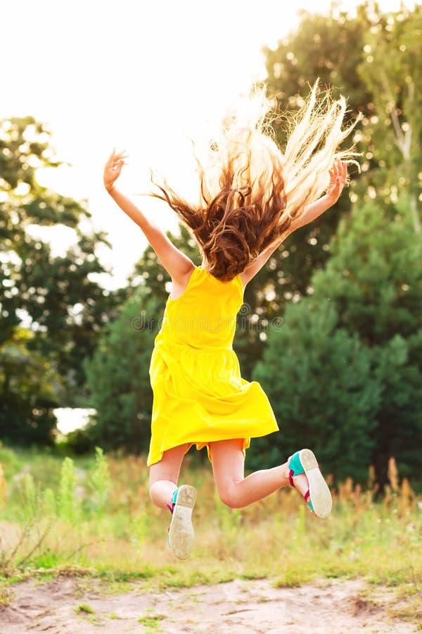 Schönes jugendlich Mädchen springt draußen bei Sommersonnenuntergang stockfotos